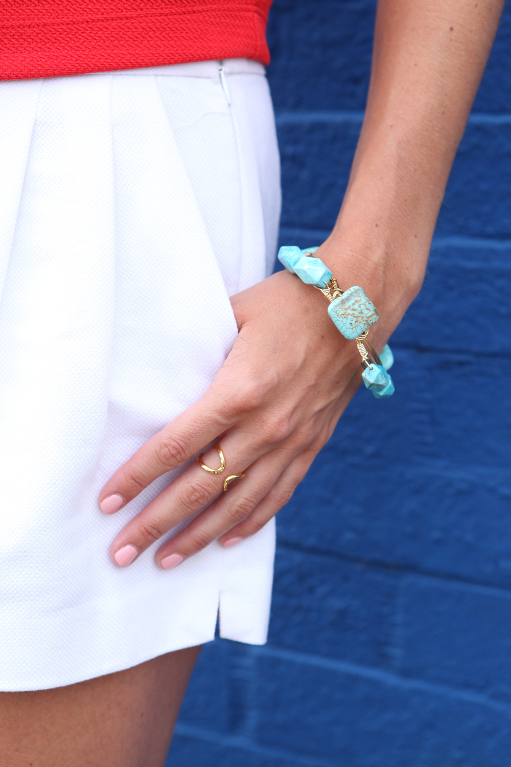 white shorts with turquoise beaded bracelet