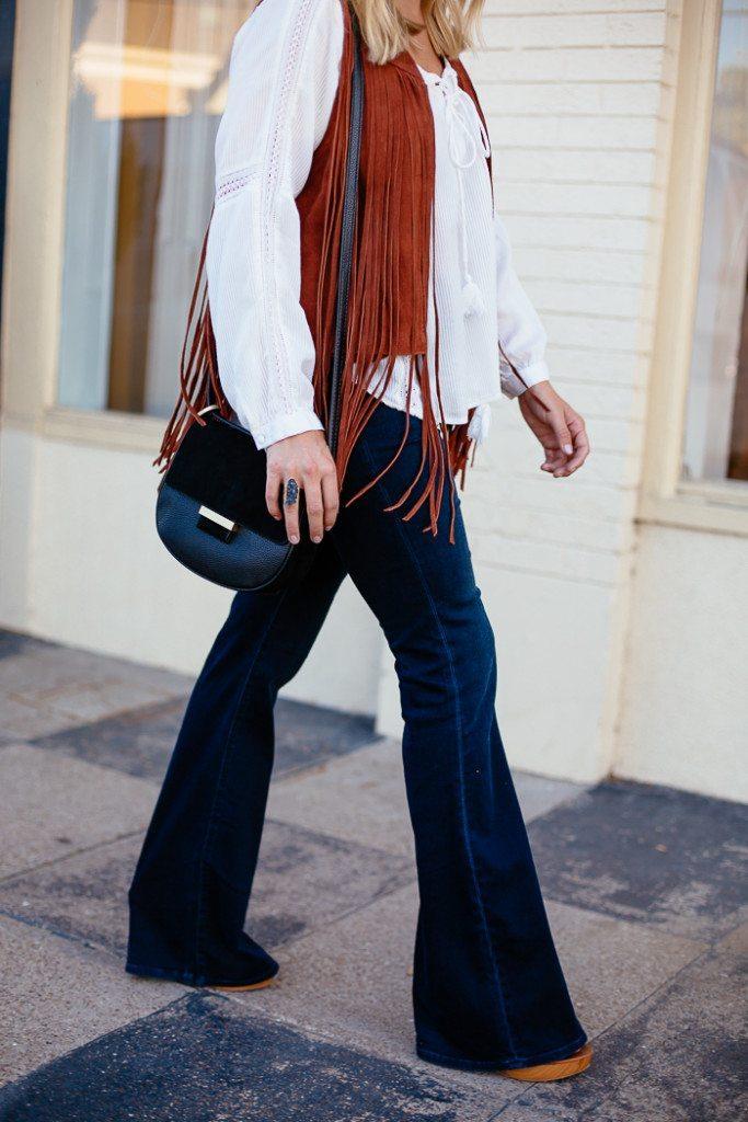 suede fringe vest-dark flare jeans-black crossbody purse-white peasant blouse