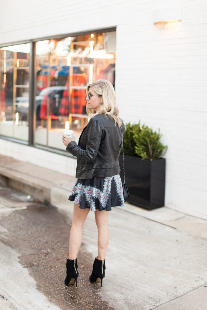 black leather moto jacket over printed dress