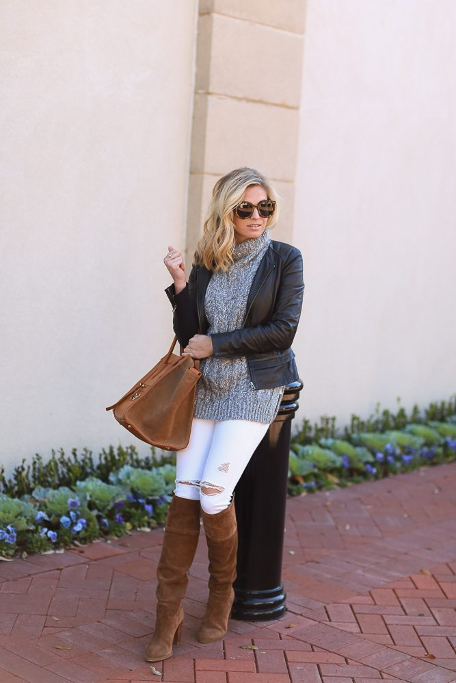 black leather jacket over grey sweater with white skinny jeans and suede over the knee boots