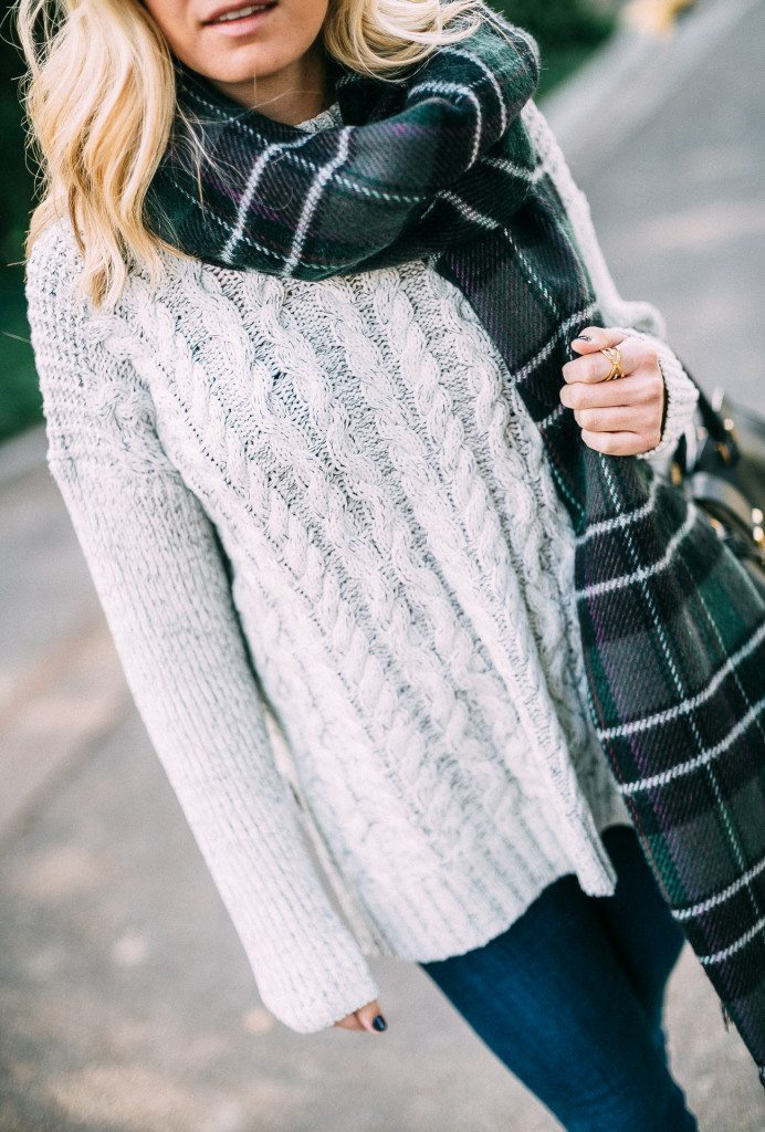 white cable knit sweater and plaid scarf