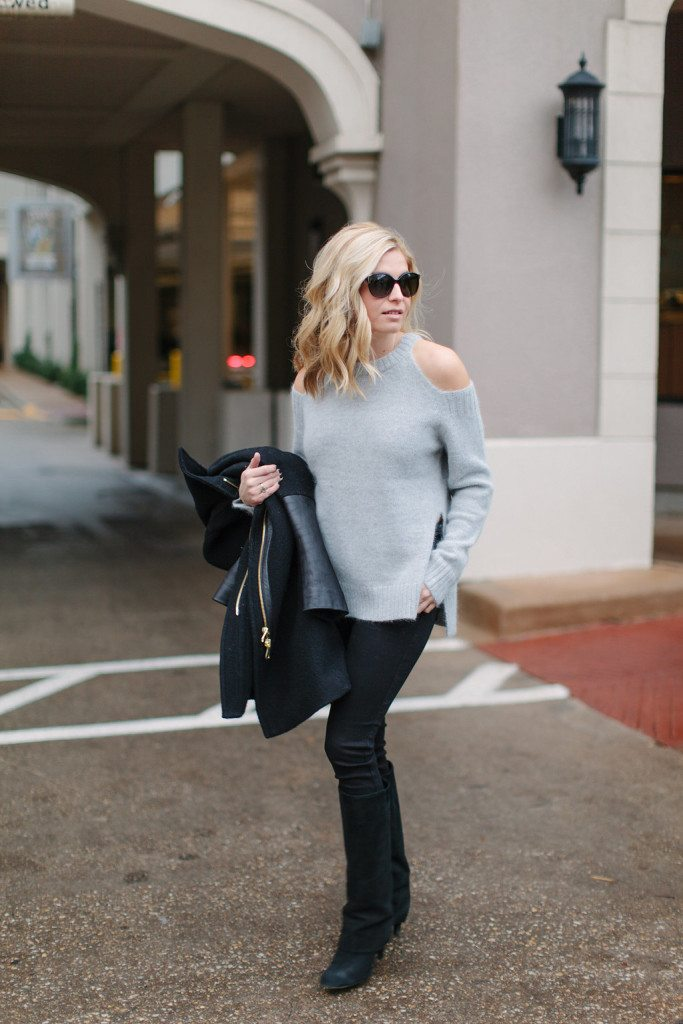 grey shoulder cut out sweater with black jeans and boots