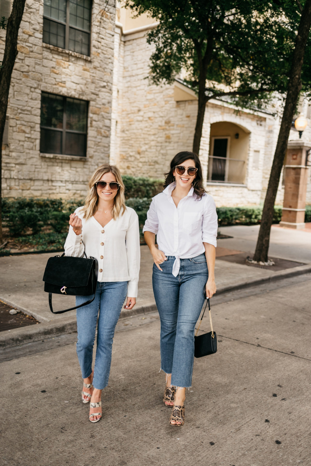 two women wearing jeans and white top