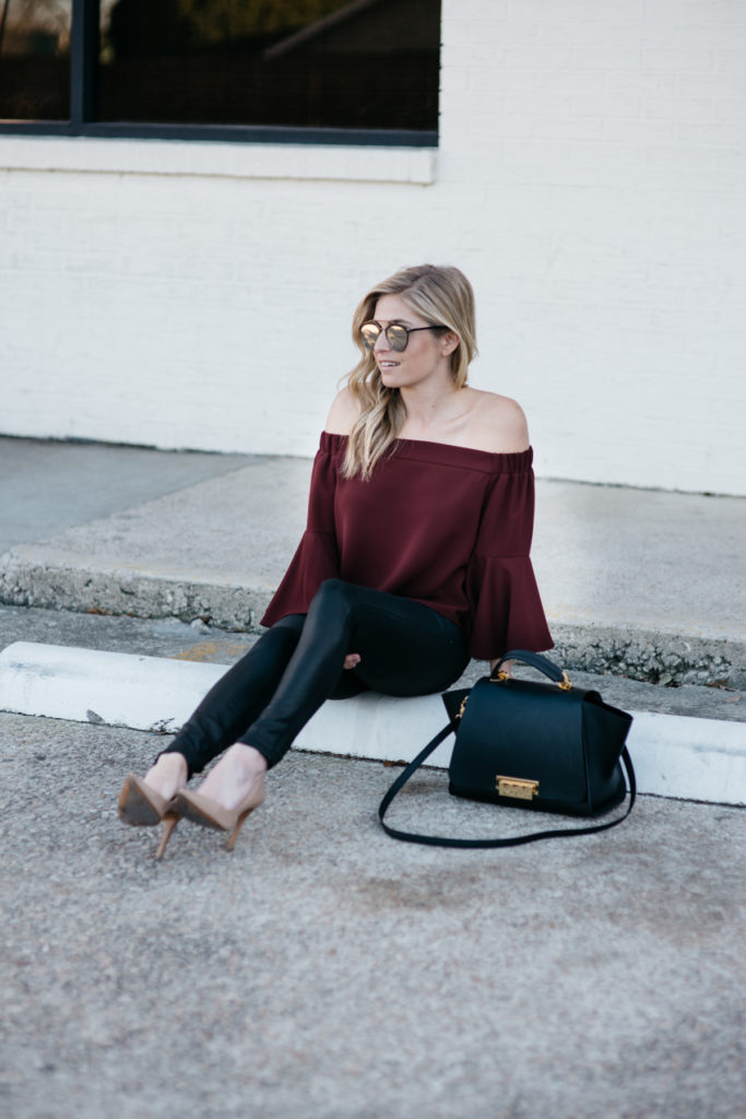 off the shoulder burgundy top, black pants, zac zac posen purse