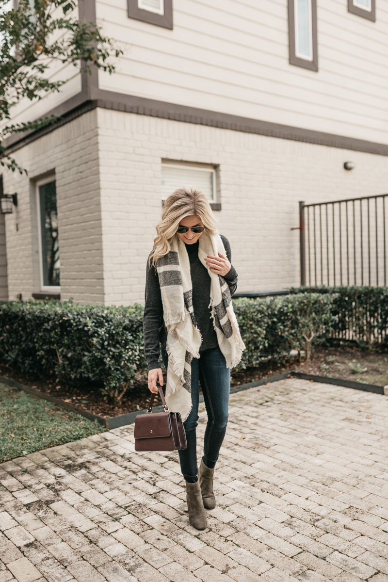 woman holding a bag and wearing cold weather accessories