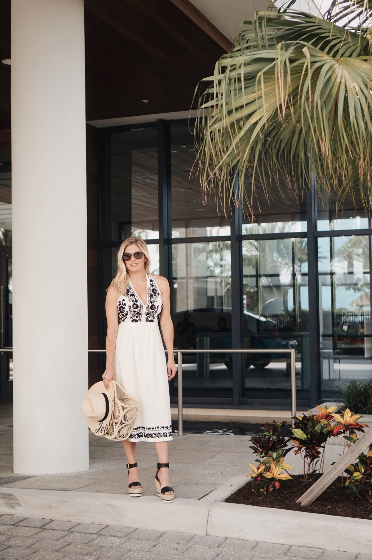 white and black embroidered midi dress paired with black wedges