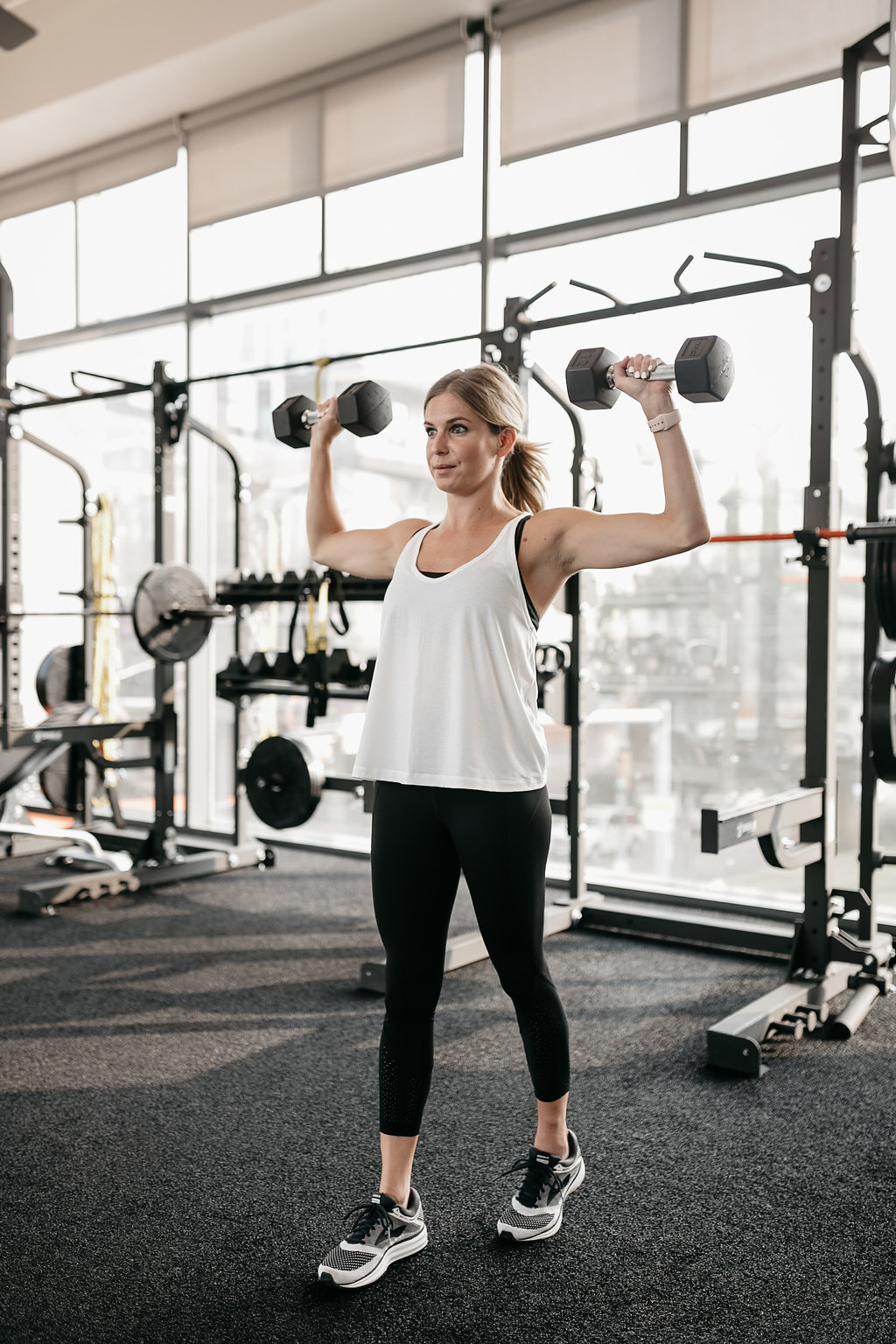 woman doing DUMBBELL OVERHEAD PRESS as exercises for toned arms