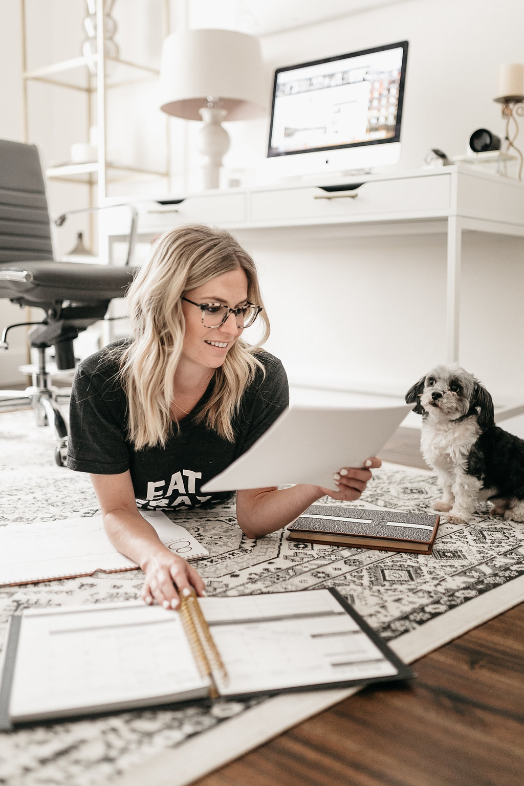 woman on the floor of her home office with her dog