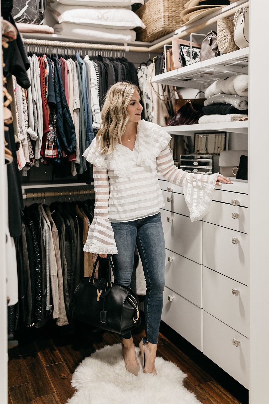 woman wearing white top and jeans with CLOSET ORGANIZATION REVEAL