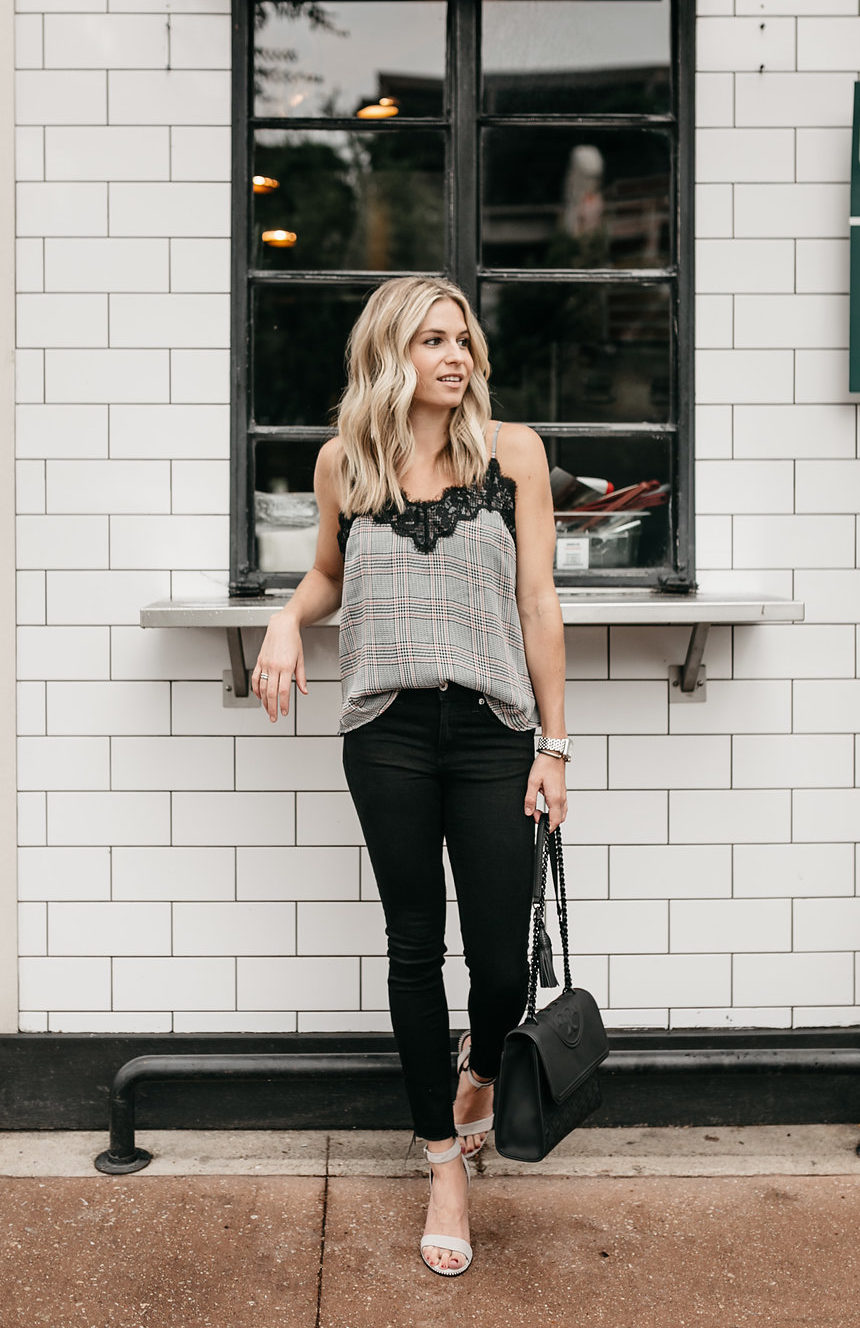 woman showing how to wear plaid, black pants, and black bag