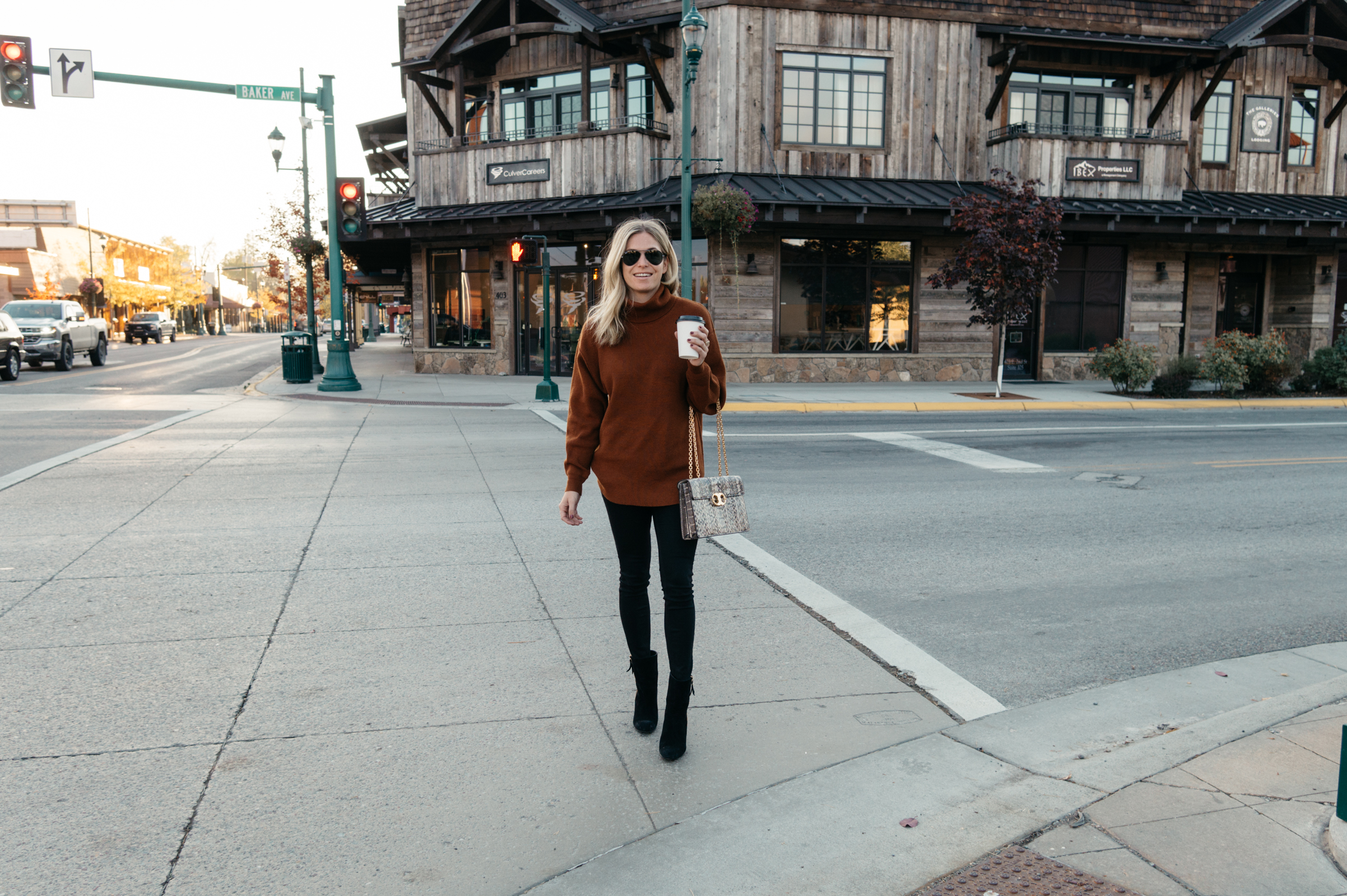 woman standing in the pedestrian and holding a coffee