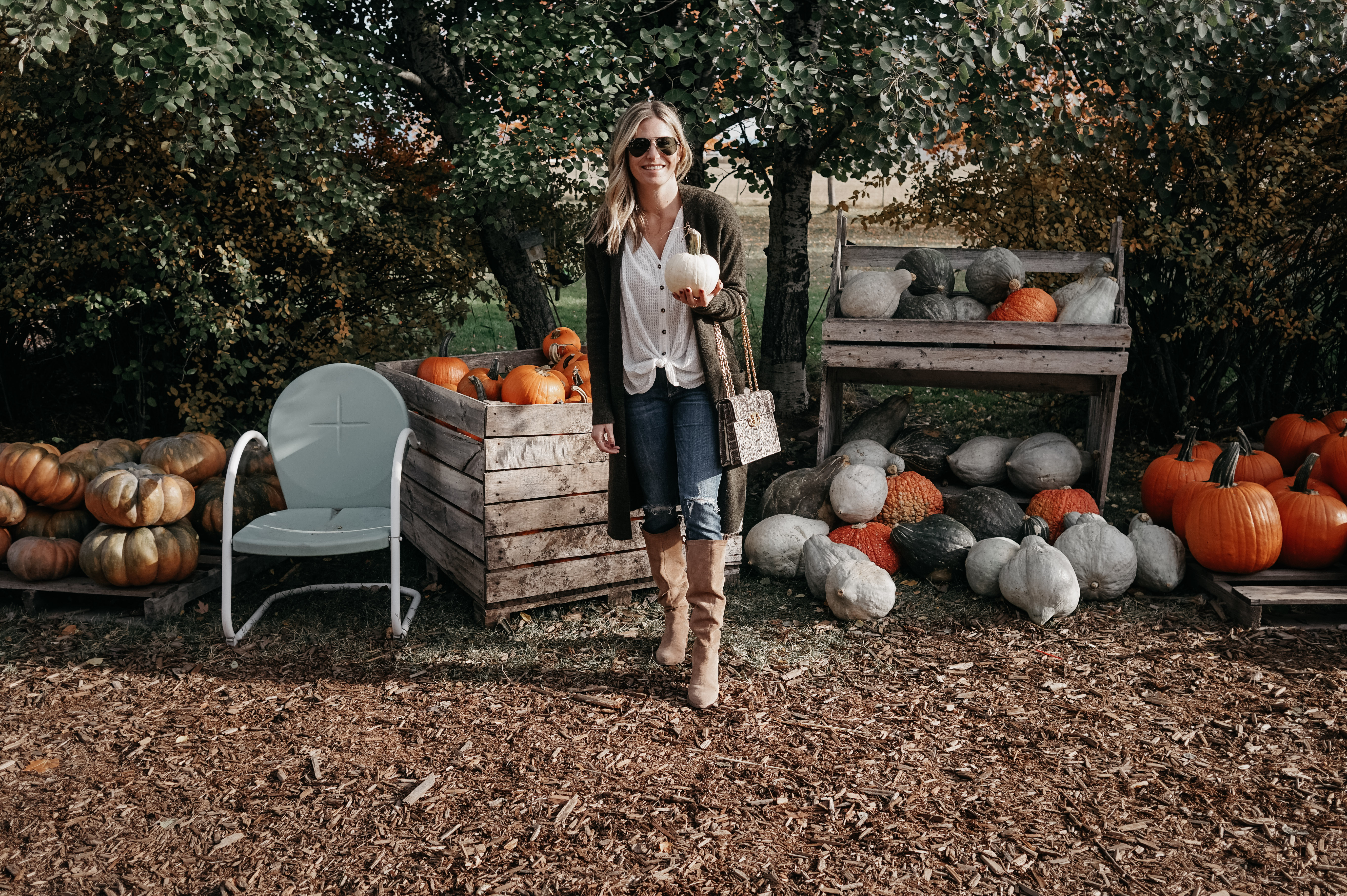 woman holding a white pumpkin with pumpkins on her background for fall in Montana