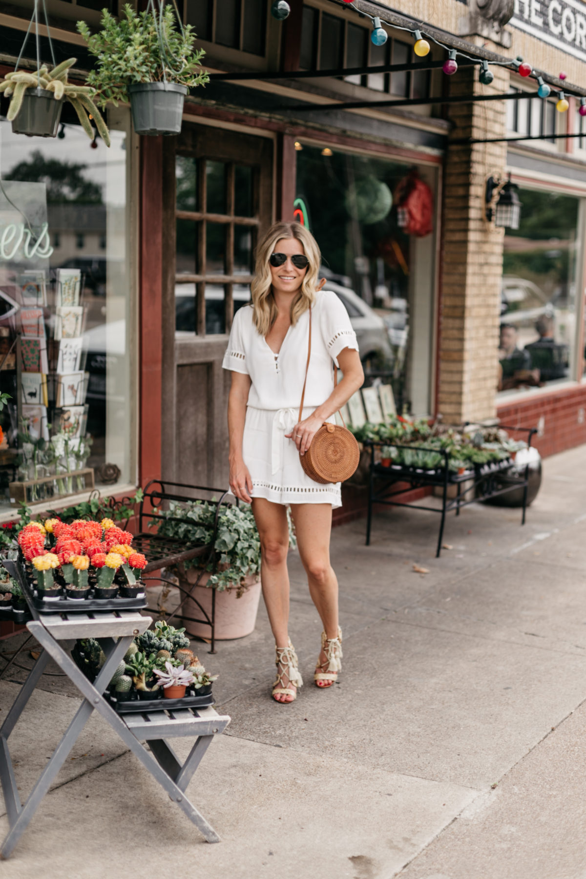 Brooke Burnett is wearing a white lace romper and woven circle bag