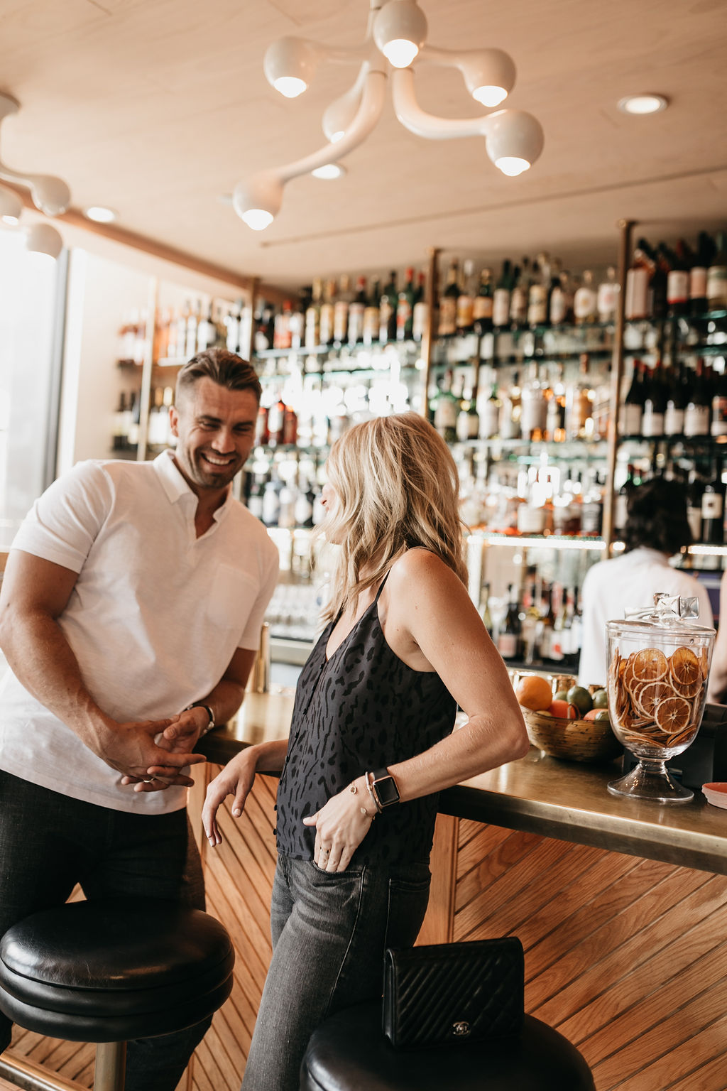 two people standing by a bar