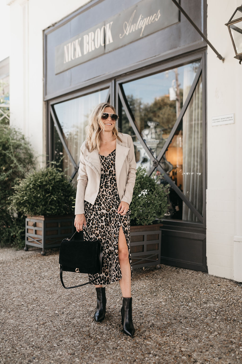 a woman in a leopard dress and leather boots