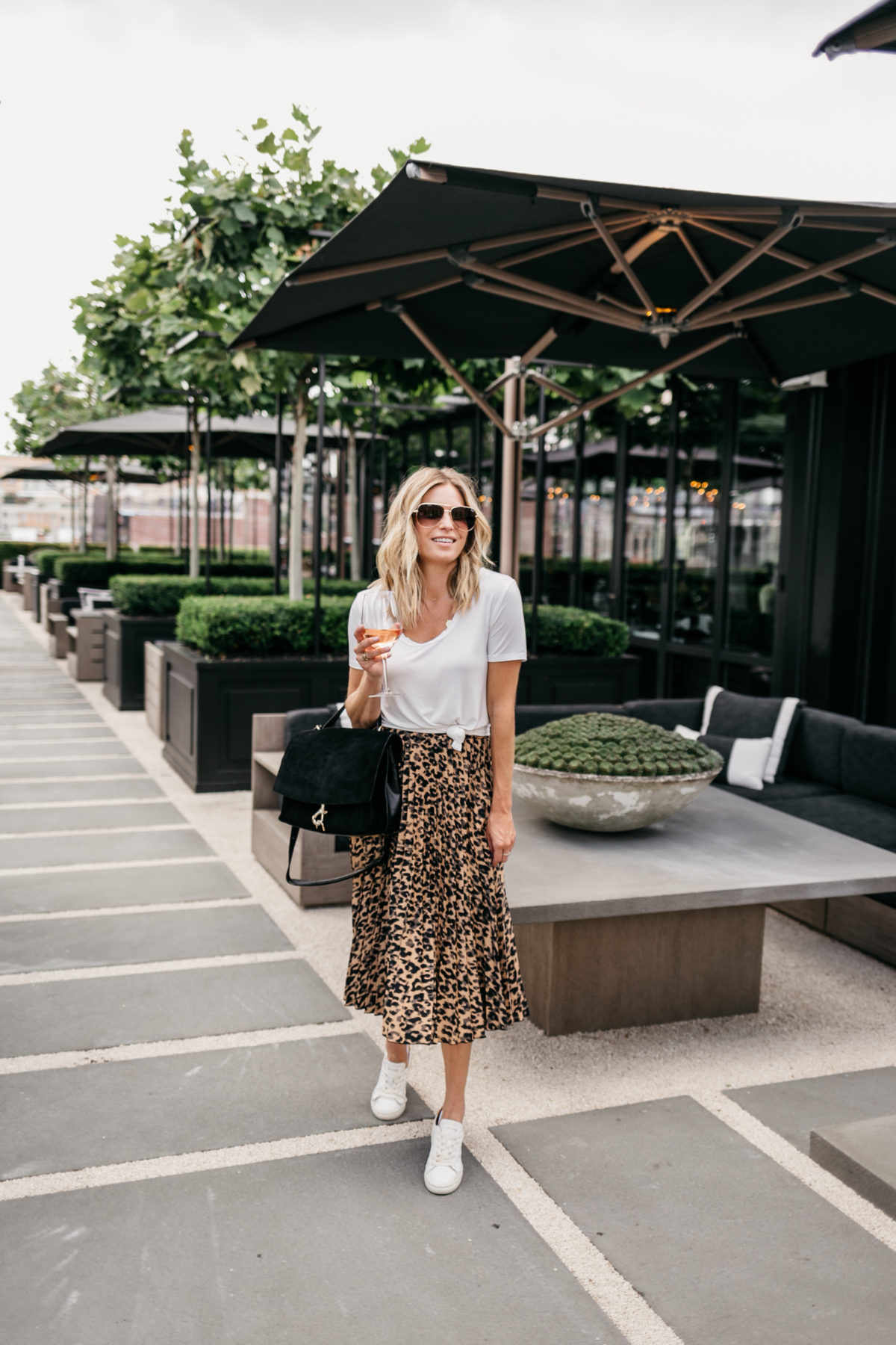 a lady in a leopard skirt and a black purse