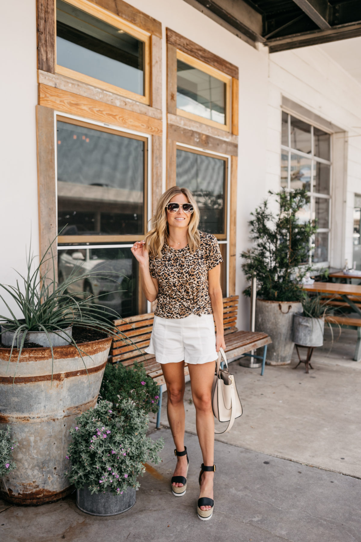 a woman in a leopard shirt and white shorts