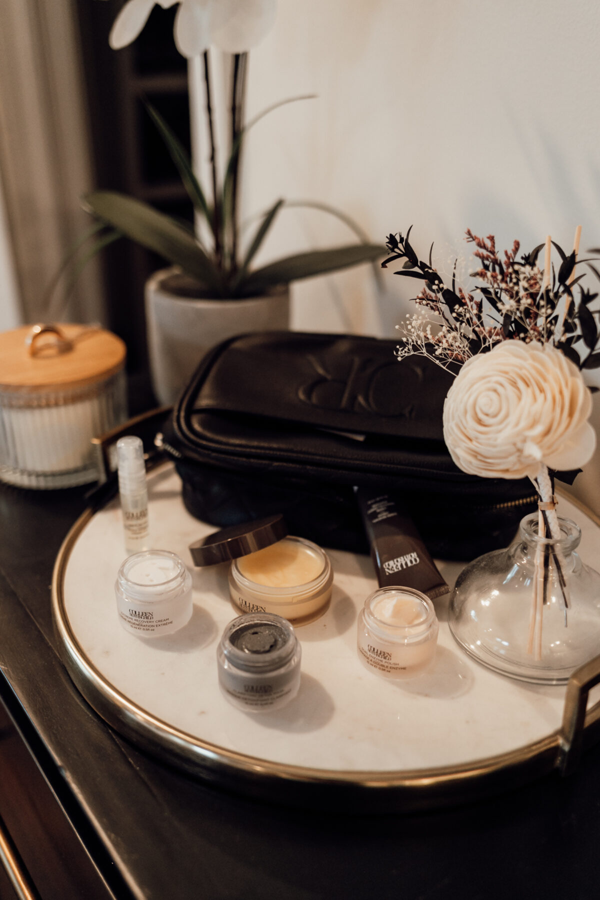 COLLEEN ROTHSCHILD BEAUTY products on top of a white tray with flowers and a black pouch