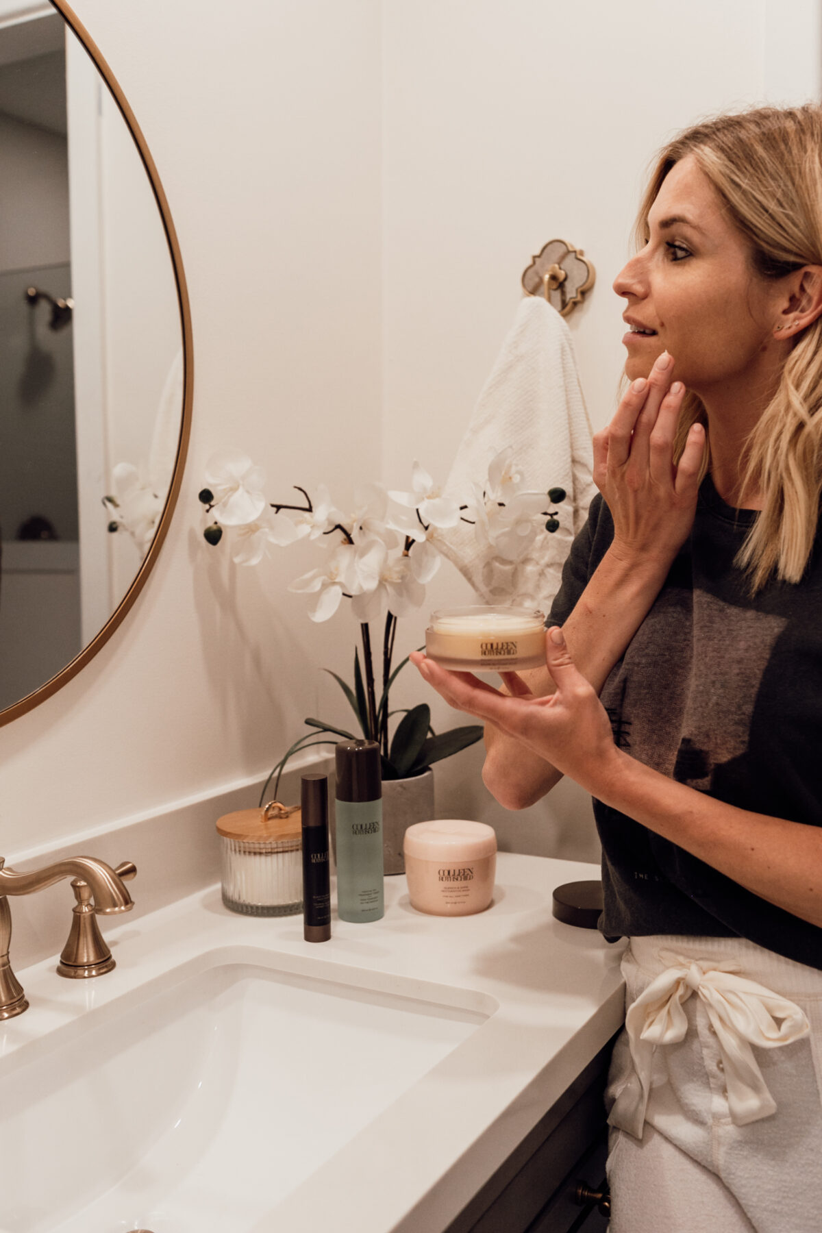 woman in the bathroom and looking at the mirror applying COLLEEN ROTHSCHILD BEAUTY