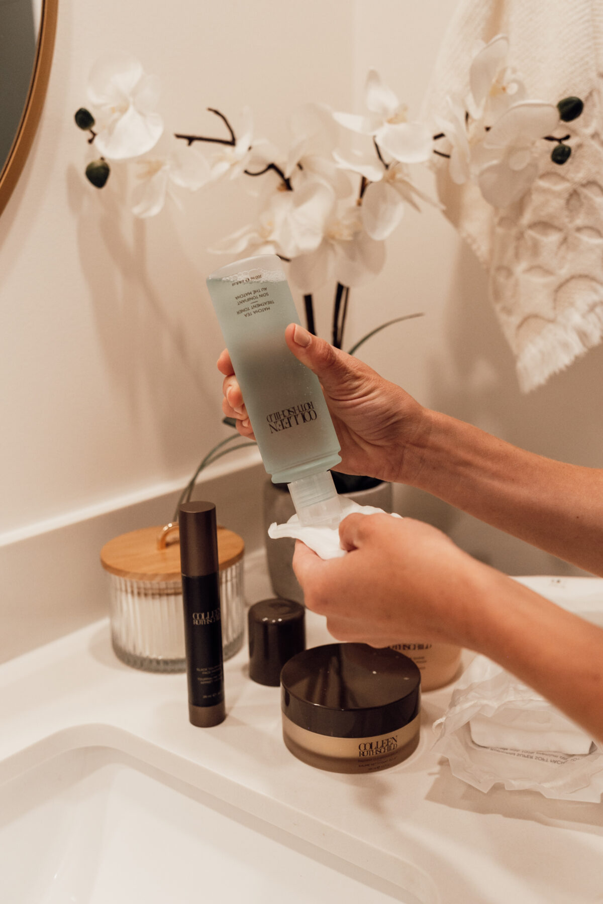 woman pouring COLLEEN ROTHSCHILD BEAUTY toner on a cotton