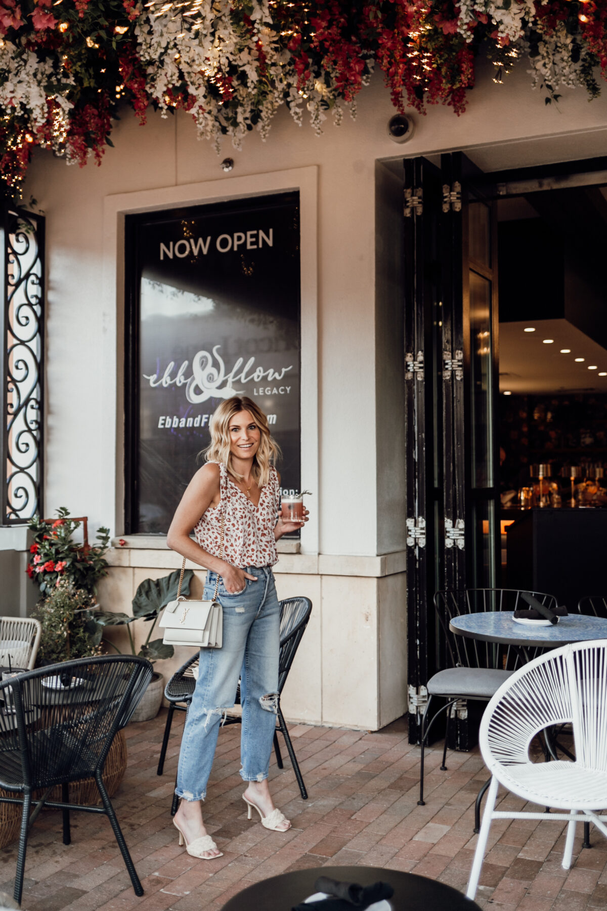 woman wearing tattered jeans and printed top for date night outfits