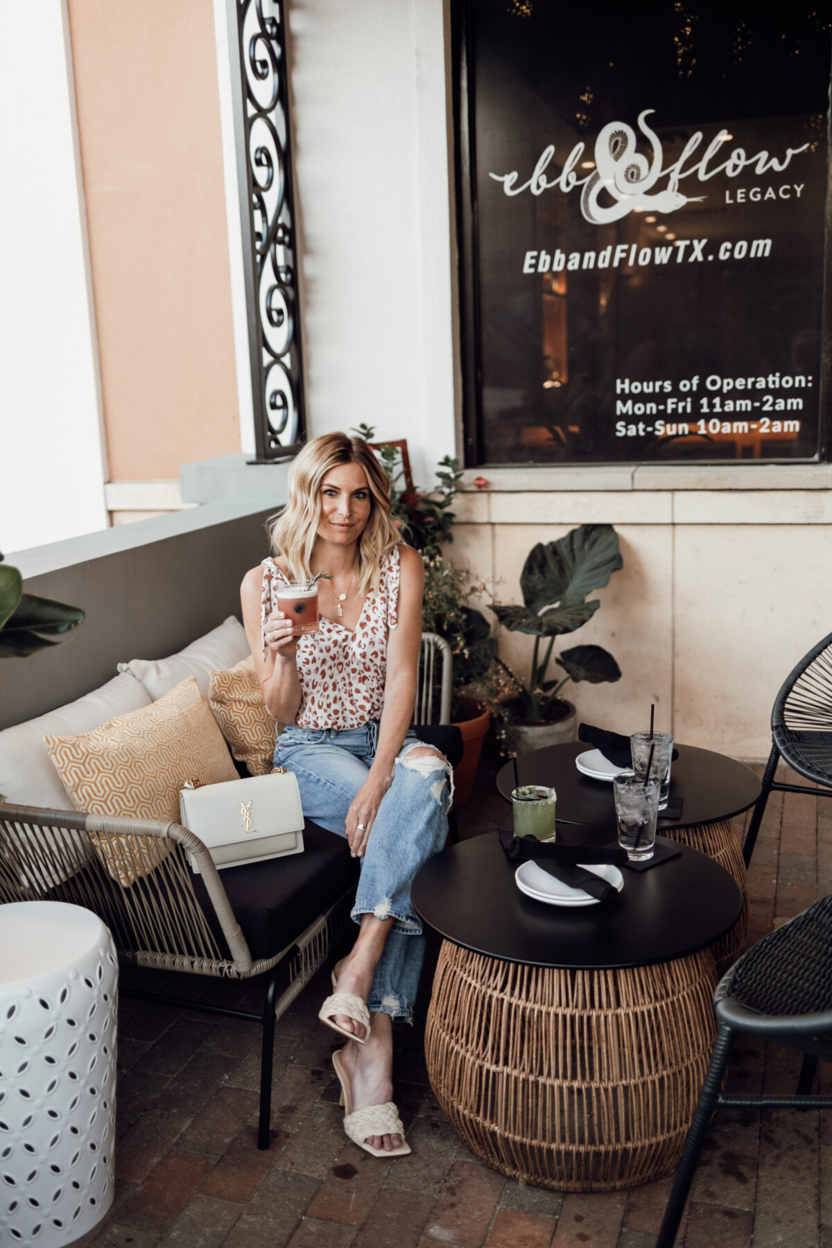 woman sitting down outside a restaurant and holding drink in her hand for date night outfits