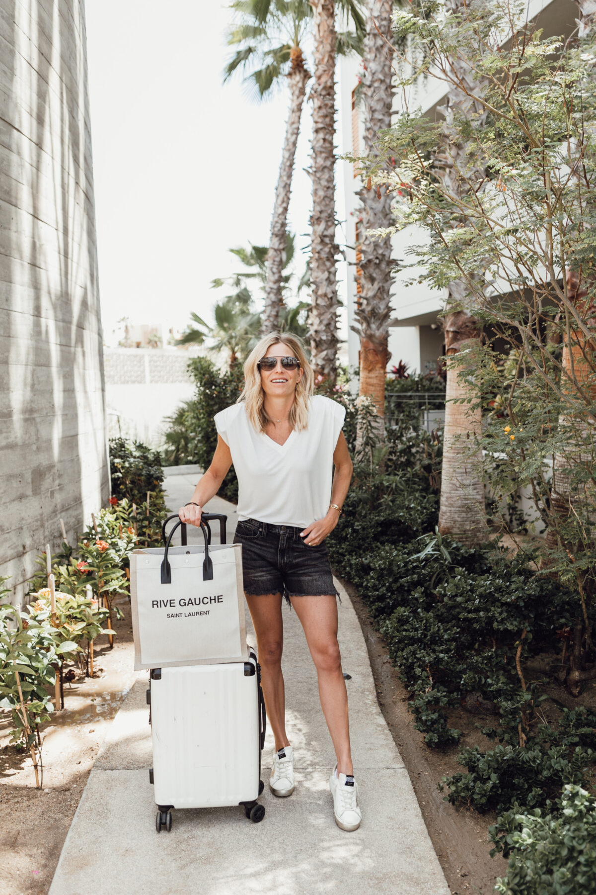 woman wearing white top and black shorts for best of april 2021 and holding a luggage
