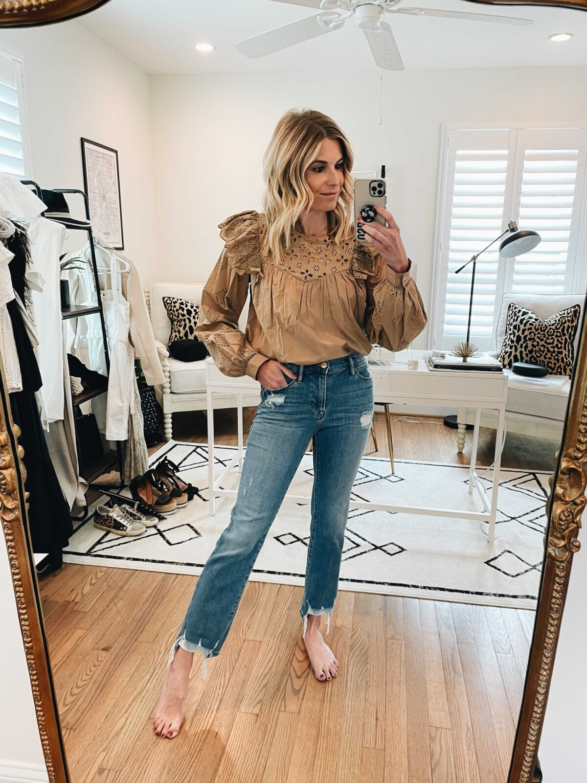 woman wearing denim jeans and brown top while taking a selfie