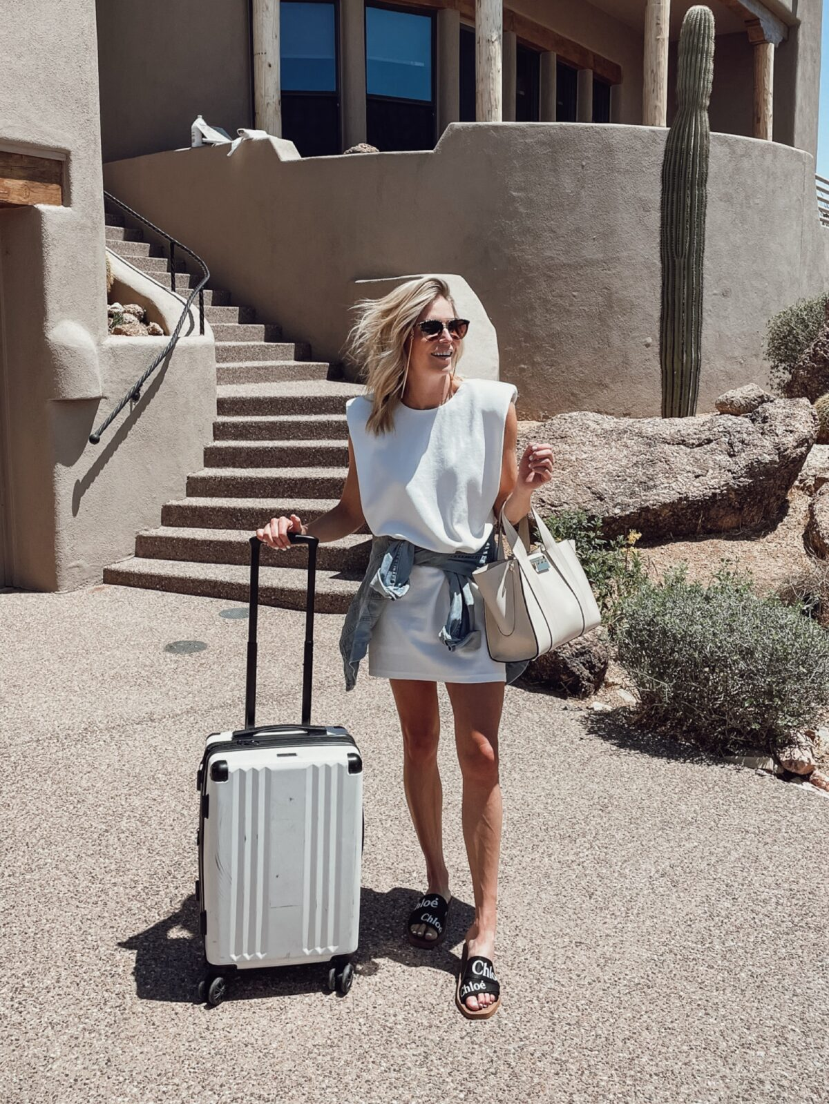 woman in white dress and holding white luggage