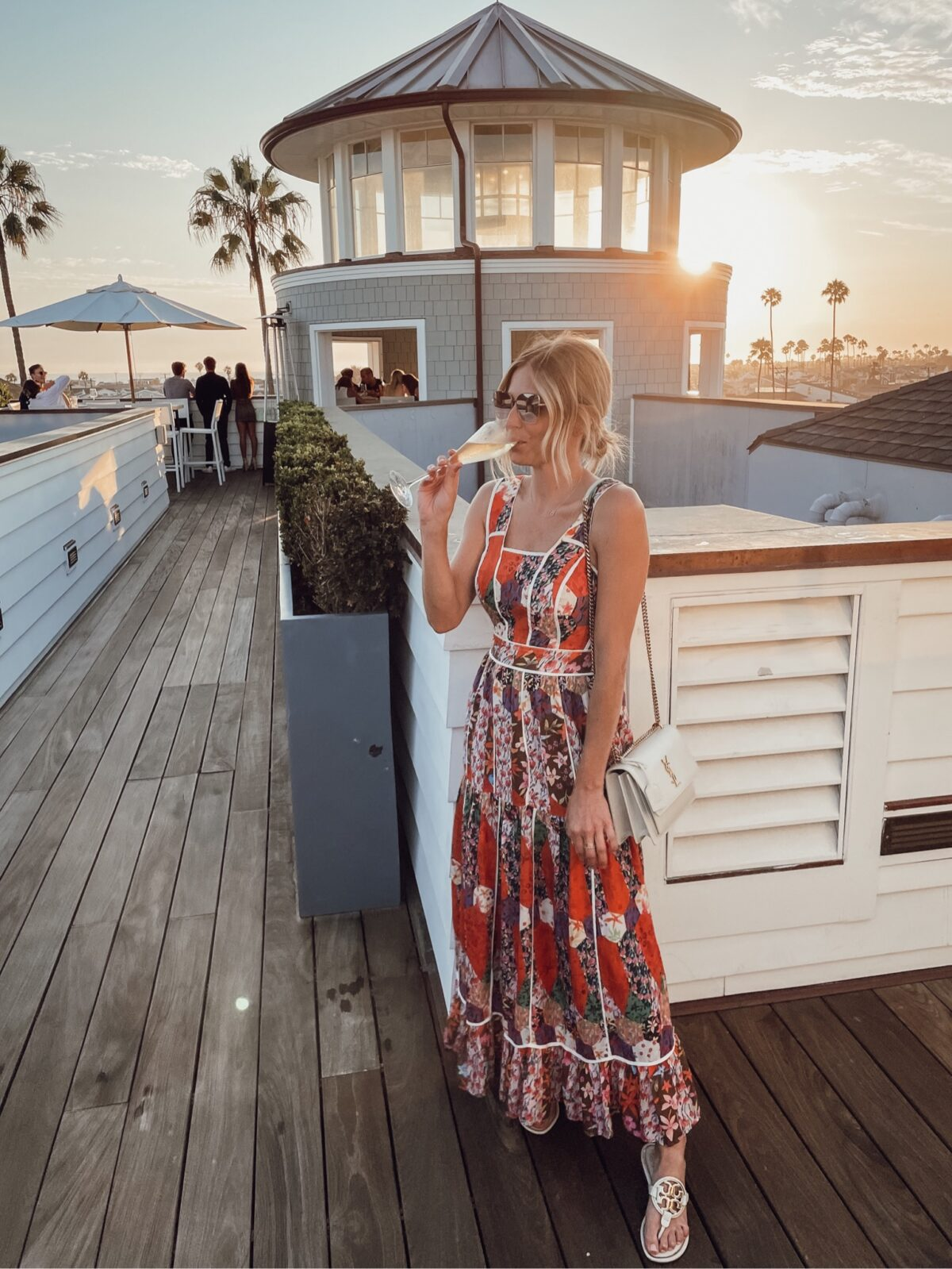 woman drinking wine and printed dress